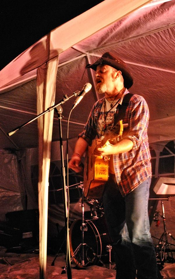"""And the rain beat down and the fire did crackle, and the brewing men did fine business..."" Going through strings on The Torch Guitar as though they were paper. Solo onstage at Farmfest, 16/08/2014. Pic by Gav Wyatt."